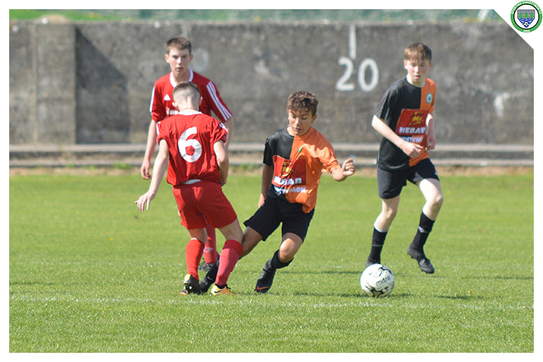 Filip Guziak is tackled late in the game between Sporting Ennistymon Football Club and Burren United Football Club. Game played on the 25th of August 2018 in Lahinch Sportsfield.