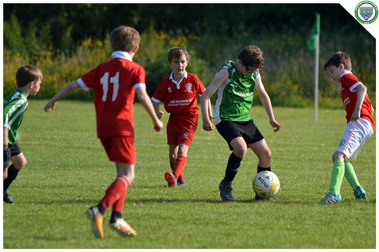 Cian Griffin takes on Newmarket Celtic defenders in the U10 game.
