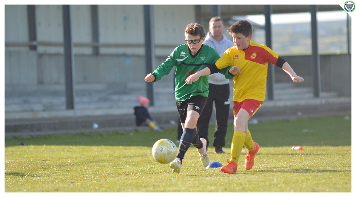 Cian Griffin dribbles up the field whilst coming under pressure from an Avenue United couterpart in the U12 game between Sporting Ennistymon Football Club and Avenue United Football Club. Game played in Lahinch Sportsfield on the 11th of June 2019.