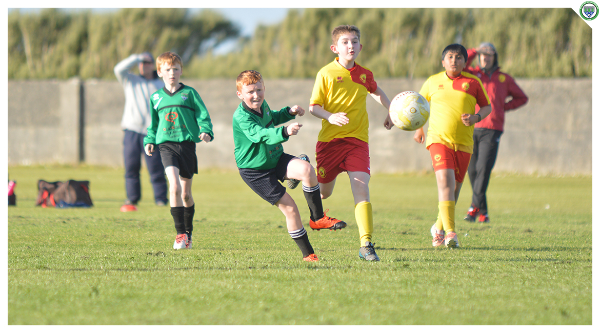 John O'Brien shoots while falling to the ground in the U12 game between Sporting Ennistymon Football Club and Avenue United Football Club. Game played in Lahinch Sportsfield on the 11th of June 2019.