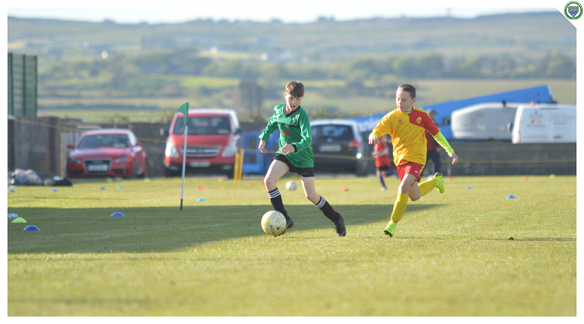 Louis Griffin dribbles up the field while coming under pressure from an Avenue United opponent in the U12 game between Sporting Ennistymon Football Club and Avenue United Football Club. Game played in Lahinch Sportsfield on the 11th of June 2019.