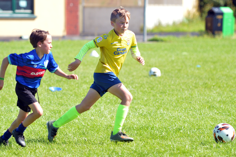 Liam Flynn dribbles against Thomas Slavin during Sporting Ennistymon F.C FAI Summer Camp 2020