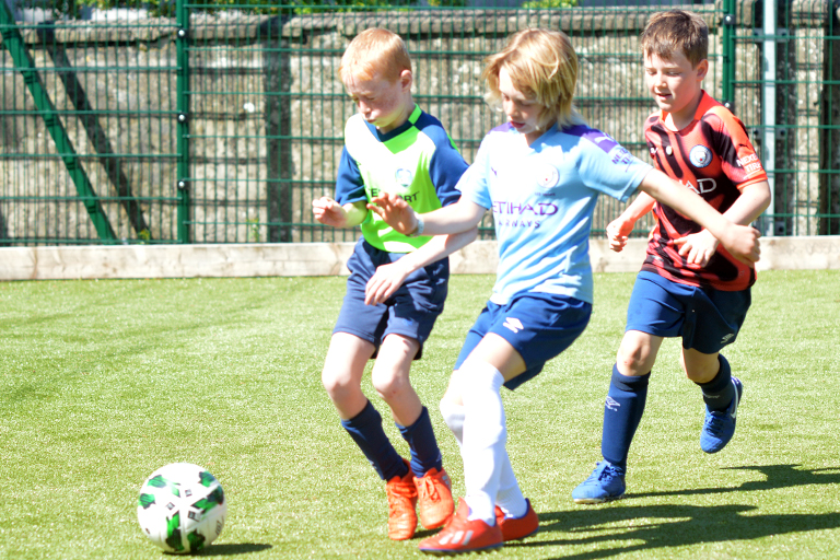 Ricky Rynne is tackled by Rian O'Malley during Sporting Ennistymon F.C FAI Summer Camp 2020