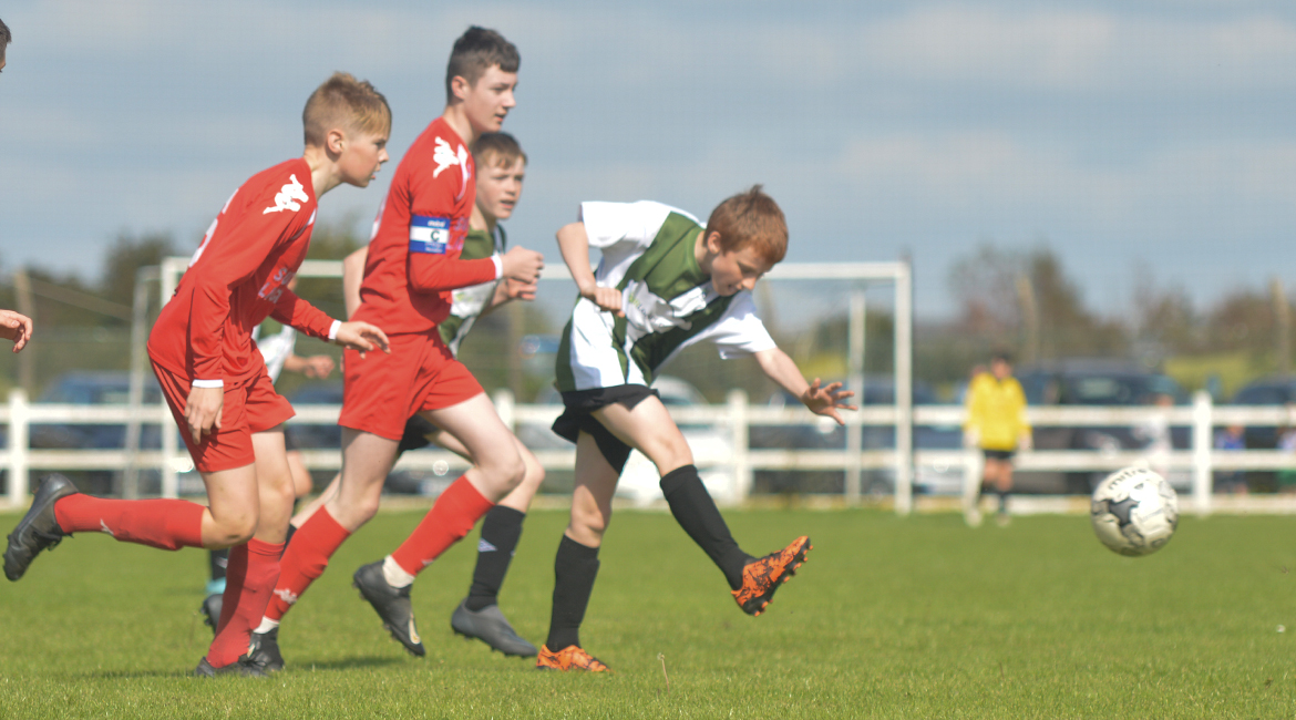 Darren O'Brien crosses a ball while coming under pressure from Lifford AFC players in the U13 Division 2 Cup Final between Sporting Ennistymon F.C and Lifford A.F.C in Frank Healy Park.